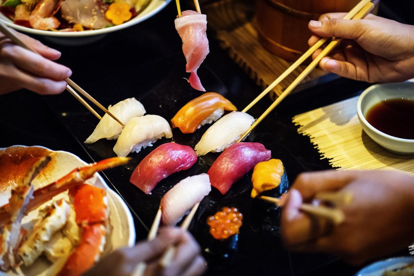Groupe d'amis qui partage un repas typiquement japonais avec des sushis et des sashimis
