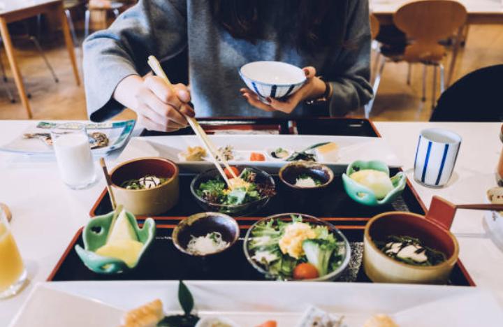 repas-japon-table-bols-baguettes-plats-algues-riz-condiments-cru-cuit